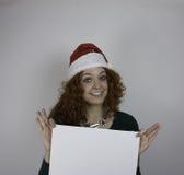 Bärande jultomtenhatt för ung kvinna som rymmer det tomma tecknet Arkivbild