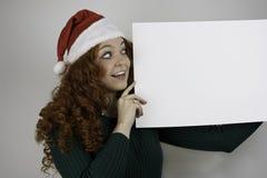 Bärande jultomtenhatt för ung kvinna som rymmer det tomma tecknet Fotografering för Bildbyråer