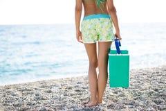 Bärande kallare ask för färdig kvinna, bärbar kyl på stranden Slank sund kvinna för passform i kortslutningar för att gå till str royaltyfri bild