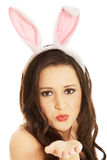 Bärande kaninöron för kvinna och blåsa en kyss Royaltyfria Foton