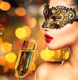 Bärande karnevalmaskering för kvinna med exponeringsglas av champagne Royaltyfri Bild