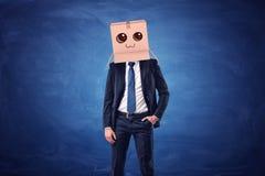 Bärande kartong för affärsman med den utdragna le framsidan på hans huvud på blå bakgrund fotografering för bildbyråer