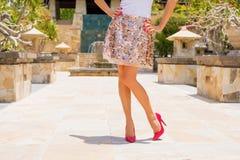 Bärande kjol för kvinna och röda höga häl royaltyfri foto