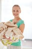 Bärande kläder för lycklig kvinna till tvätterit hemma Royaltyfri Bild