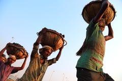 Bärande kolkorg för man på huvudet Royaltyfri Foto