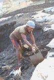 Bärande kolkorg för man på huvudet Arkivfoto