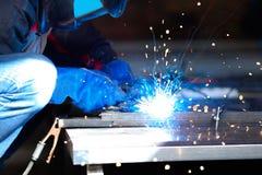 Bärande konstruktionshandskar för manlig arbetare som svetsar metallkonstruktion, blå svetsningbåge Fotografering för Bildbyråer