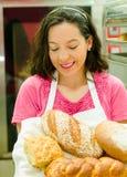Bärande korg för bageriarbetare av bröd, medan le lyckligt Royaltyfria Foton