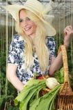 Bärande korg för lycklig blond kvinna av grönsaker Royaltyfri Fotografi