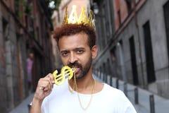 Bärande krona för man och halsband för dollartecken royaltyfri fotografi