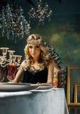 Bärande krona för ung blond kvinna i felik lyxig inre med em Royaltyfri Foto