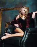 Bärande krona för ung blond kvinna i felik lyxig inre med em Royaltyfria Bilder