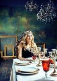 Bärande krona för ung blond kvinna i felik lyxig inre med em Arkivbild