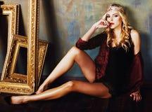 Bärande krona för ung blond kvinna i felik lyxig inre med em Royaltyfria Foton