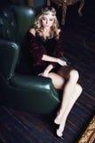 Bärande krona för ung blond kvinna i felik lyxig inre med em arkivfoto
