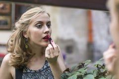 Bärande läppstift för härlig kvinna nära spegeln Arkivfoton