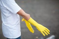 Bärande latexhandske för att göra ren förestående på asfaltbakgrund Racka ner på på den tillbaka sidan arkivfoton