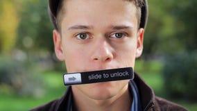 Bärande lock för gullig pojke som ser kameran med ID-Märket sticked till hans mun arkivfilmer