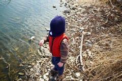 Bärande lockanseende för ungt barn vid vatten arkivfoto