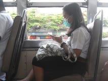 Bärande maskering för flicka på bussen PM2 luftförorening för damm 5 bangkok thailand royaltyfri fotografi