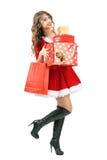 Bärande massor för lycklig upphetsad härlig Santa Claus kvinna av att gå för julgåvor Royaltyfri Bild