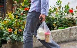Bärande mellanmål för Yuong man av kaffe och bröd i plast- shoppa påsar för kast-bort royaltyfri fotografi