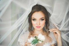 Bärande modebröllopsklänning för härlig brud med fjädrar med det lyxiga fröjdsminket och frisyren, studio inomhus Royaltyfri Fotografi
