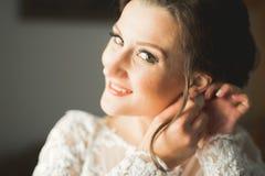 Bärande modebröllopsklänning för härlig brud med fjädrar med det lyxiga fröjdsminket och frisyren, studio inomhus arkivbilder