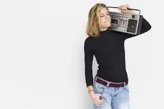 Bärande och lyssnande musik för kvinna vid radion arkivfoton