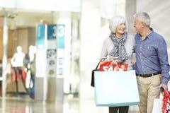 Bärande påsar för lyckliga höga par i shoppinggalleria royaltyfria foton