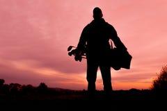 Bärande påse för golfare på solnedgången Arkivbild