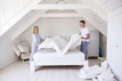 Bärande pyjamas för par som gör säng i morgon royaltyfria bilder