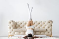Bärande pyjamas för ung kvinna som lyssnar till musik i inre ljust rum arkivfoto