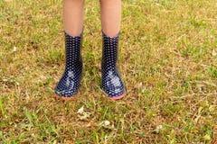 Bärande regnkängor för barn på gräset Arkivfoton