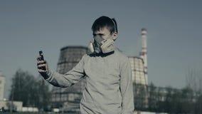Bärande respirator för ung pojke genom att använda mobiltelefonen mot fabrikslampglas Luftf?roreningbegrepp chernobyl arkivfilmer