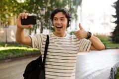 Bärande ryggsäck för upphetsad tillfällig man på stadsgatan royaltyfri fotografi