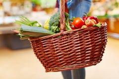 Bärande shoppingkorg för kund med grönsaker Royaltyfri Bild