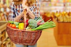 Bärande shoppingkorg för kvinna i supermarket fotografering för bildbyråer