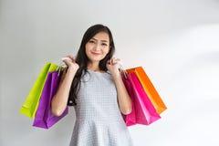 Bärande shoppingpåsar för härlig asiatisk flicka bakgrund som isoleras över le vit kvinna för shopping asiatisk härlig flicka Ung royaltyfri bild