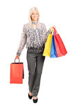 Bärande shoppingpåsar för trendig kvinna Royaltyfri Bild