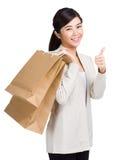 Bärande shoppingpåse och tumme för kvinna upp Royaltyfri Bild