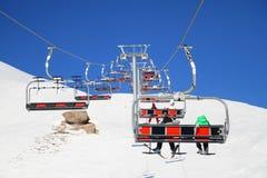 Bärande skidåkare för skidlift, snowboarders på en ljus solig vinterdag Royaltyfri Fotografi