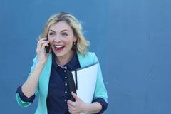 Bärande skolaanmärkningar och penna för extatisk ung flicka, medan tala på en telefon som isoleras på blå bakgrund Arkivbilder