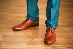 Bärande skor för man på trägolv Klädbegrepp, brudgum som får klar för ceremoni Kroppdetalj av affärsmannen royaltyfri fotografi
