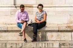 Bärande solglasögon för Caucasian par som sitter och vilar på sandstentrappa i den Budapest Ungern Fotografering för Bildbyråer