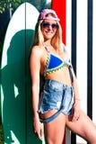 Bärande solglasögon för charmig blond flickasurfare som poserar i sommar med bränning Fotografering för Bildbyråer