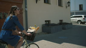 Bärande solglasögon för flicka med att vinka mörkt hår som cyklar nära byggnader Bilar som parkeras nära vägen, långsam mo, stedi stock video