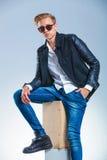 Bärande solglasögon för grabb och läderomslag, medan ha hans hand royaltyfri fotografi