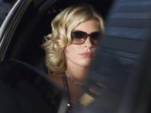 Bärande solglasögon för kvinna i limousine arkivfoton