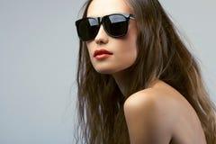 Bärande solglasögon för kvinnastående arkivbilder